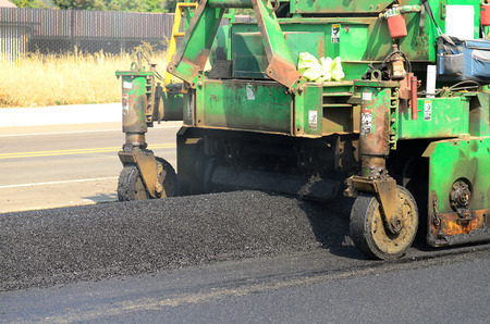 asphalt paving: Asphalt paving machine laying down a fresh layer of paving on a new road interchange project