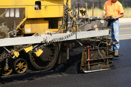 Asphalt paving machine laying down a fresh layer of paving on a new road interchange project