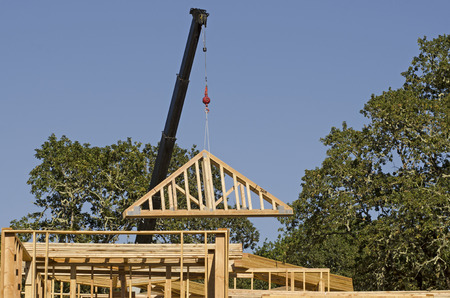 rafter: Roof truss company placing new home wood engineered trusses on a residential construction site