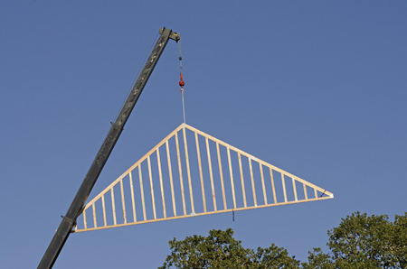 Roof truss company placing new home wood engineered trusses on a residential construction site