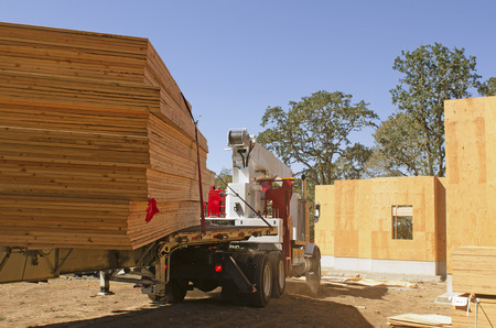engineered: Roof truss company arrives with new home wood engineered trusses at a residential construction site