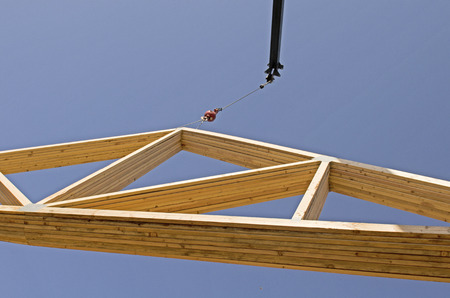 Roof truss company placing new home wood engineered trusses on a residential construction site Stock Photo - 38671859