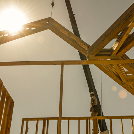 roof truss company placing new home wood engineered trusses on a residential construction site stock photo - 84 Lumber Roof Trusses