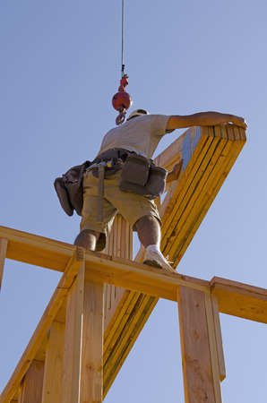 engineered: Roof truss company placing new home wood engineered trusses on a residential construction site