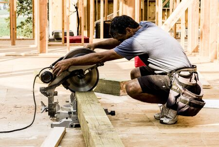 miter: Framing contractor using a circular hand saw to trim wood beam to length.