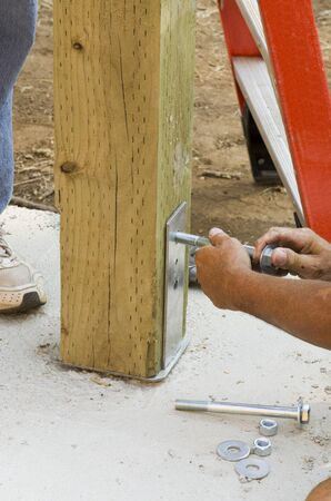 treated board: Installing a bolt in a hole to accommodate  a post on a new luxury custom home Stock Photo