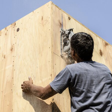 framer: Framing construction contractor installing a beam pocket on a wood frame wall of a new luxury custom home