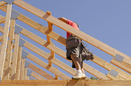 contractor: Building contractor carpenter placing new home wood engineered trusses on a residential construction site