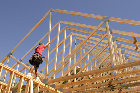 builder: Carpintero contratista de construcci�n colocando nuevas madera casa cerchas de ingenier�a en un sitio de construcci�n de viviendas