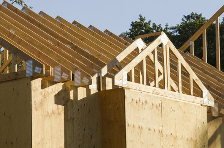 Building contractor carpenter placing new home wood engineered trusses on a residential construction site Stock Photo - 39058207