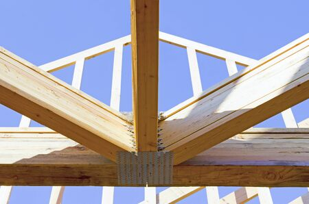 engineered: Building contractor carpenter placing new home wood engineered trusses on a residential construction site