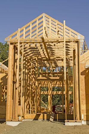 single family: A single family home under construction. The house has been framed and covered in plywood and roof trusses in place. Stock Photo