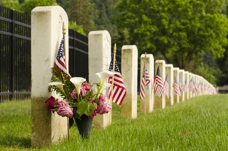 장례식 날 동안 미국 군사 참전 용사의 마지막 휴식 무덤에 놓인 깃발들