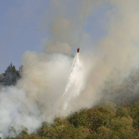 suppress: Roseburg, OR, USA - September 12, 2014: Fire fighters work with aviation helicopters to suppress a natural cover brush and grass fire in southern Oregon