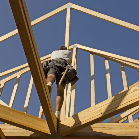 rafter: Building contractor carpenter placing new home wood engineered trusses on a residential construction site