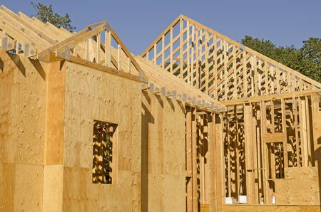 single family home: A single family home under construction. The house has been framed and covered in plywood and roof trusses in place. Stock Photo