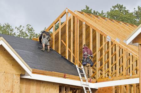 Bautrupp Arbeiten am Dachbahnen aus einem neuen, luxuriösen Wohnhaus-Projekt in Oregon Standard-Bild - 39569281