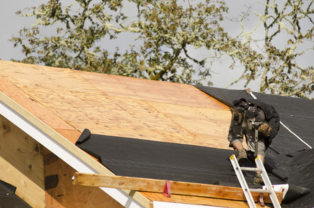 Construction crew working on the roof sheeting of a new, luxury residential home project in Oregon