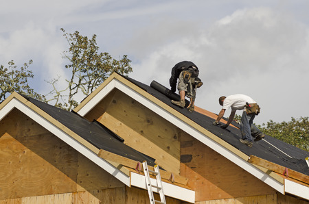 construction crew: Construction crew working on the roof sheeting of a new, luxury residential home project in Oregon