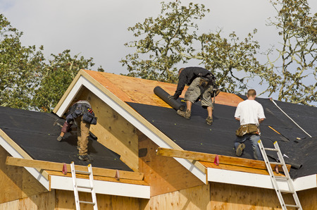 roofer: Construction crew working on the roof sheeting of a new, luxury residential home project in Oregon