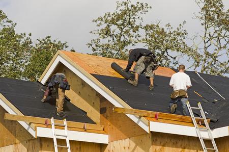 constructor: Equipo de construcción que trabaja en las láminas del techo de un proyecto de la casa residencial nueva, de lujo en Oregon Foto de archivo