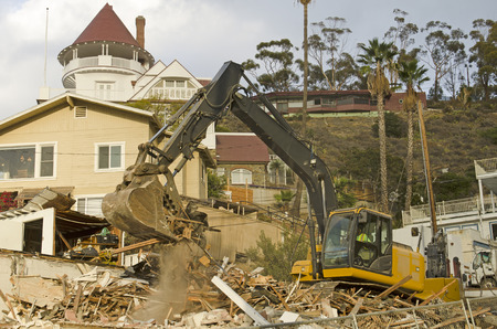 tearing down: Tracked excavator tearing down an old house harbor at the port of Avalon on Catalina Island California Stock Photo