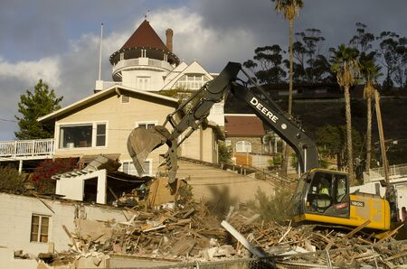 tearing down: Tracked excavator tearing down an old house harbor at the port of Avalon on Catalina Island, California Stock Photo