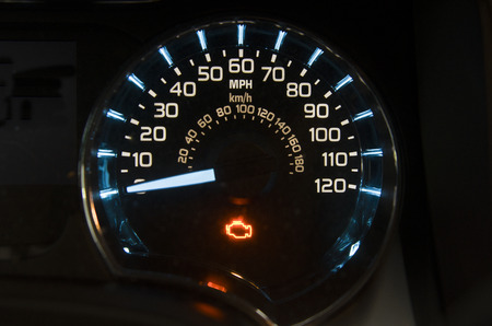 Check engine light on on a  speed gauge of a modern vehicle