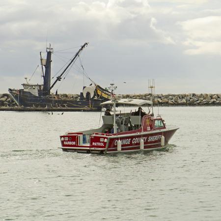 orange county: Orange County Sheriff patrol boat exits Dana Harbor California on a winter morning