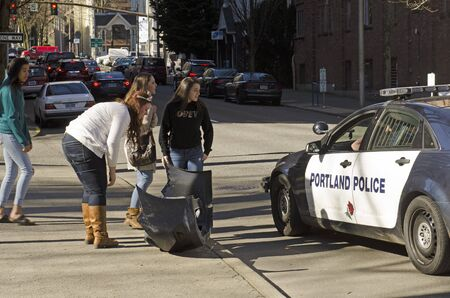 motor cop: Portland, OR, USA - February 21, 2014: Group of young girls discuss an minor vehicle accident with Portland Oregon Police officer