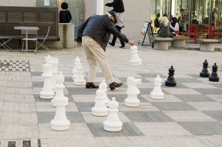 south park: Portland, OR, USA - February 21, 2014: A man plays chess with giant pieces in Simon and Helen Director Park, South Park Blocks