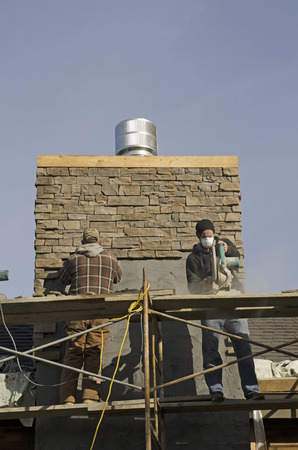 masonary: Masonary contractor using scafolding to place grout for dry tile or rock siding for a home chimney installation Editorial