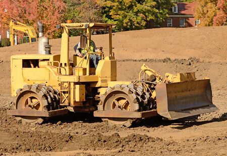 vibroroller: Large steel wheeled compactor working the ground at a new commercial housing development