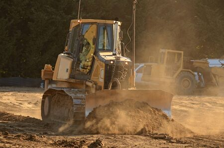 housing development: Small bulldozer moving rock and soil in a new commercial housing development Stock Photo