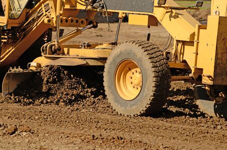 grader: Large road grader working ground at a new commercial housing development Stock Photo