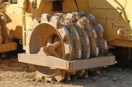 construction vibroroller: Large steel wheeled compactor working the ground at a new commercial housing development