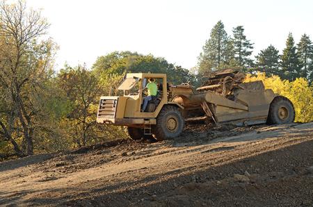 housing development: Large construction scraper moving soil for a new commercial housing development Stock Photo