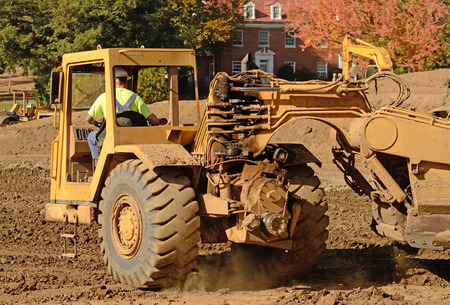 earthmover: Large construction scraper moving soil for a new commercial housing development Stock Photo