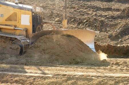 earthmover: Small bulldozer moving rock and soil in a new commercial housing development Stock Photo