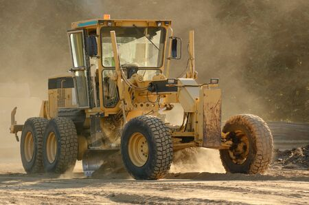 scrapers: Large road grader working ground at a new commercial housing development Stock Photo