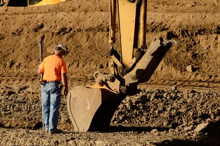 trenches: Excavator track hoe diging foundation trenches at a new commercial housing development Stock Photo