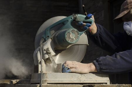 masonary: Masonary contractor using a dry circular tile or rock cutting saw to trim rock siding for a home installation Stock Photo