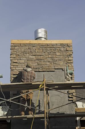 masonary: Masonary contractor using scafolding to place grout for dry tile or rock siding for a home chimney installation Stock Photo