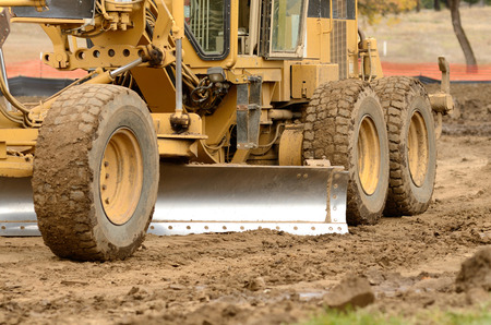 grader: Large surface grader tractor works at moving soil and rock for a new commercial housing development. Stock Photo