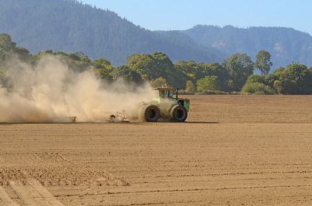 A large tractor doing final soil prep using a disc harrow before planting