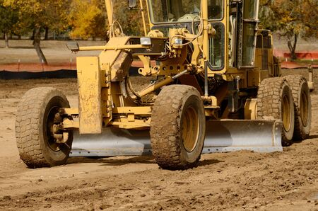 machinery: Large surface grader tractor works at moving soil and rock for a new commercial housing development. Stock Photo