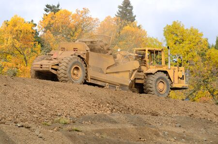 earthmover: Large box scraper tractor works at moving soil and rock for a new commercial housing development. Stock Photo