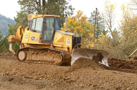 housing development: Bulldozer tractor works at moving soil and rock for a new commercial housing development. Stock Photo