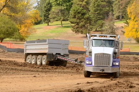 housing development: A tandom dump truck works at moving soil and rock for a new commercial housing development.