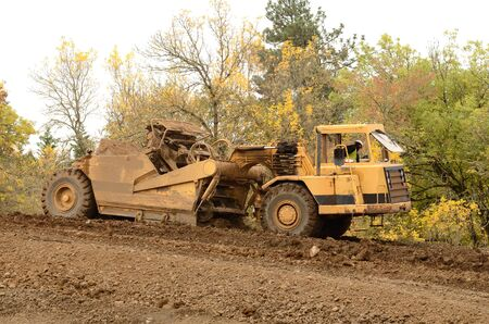Large box scraper tractor works at moving soil and rock for a new commercial housing development. Standard-Bild